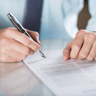 A man's hands signing business documents